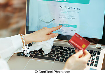woman with empty blister buying pharma using laptop touch screen