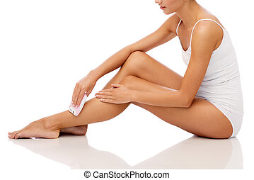 woman with epilator removing hair on legs - people, beauty,...