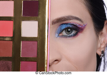 Woman with evening make-up holds eye shadow palette closeup