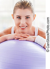 Woman with exercise ball. Beautiful mature woman leaning at fitness ball and smiling