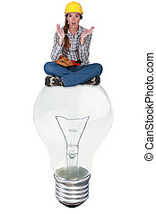 Woman with expression of surprise sat on a big light bulb