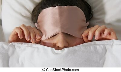 woman with eye sleeping mask in bed under blanket