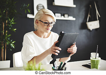 Woman with eyeglasses using a digital tablet