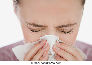 Woman with eyes closed blowing her nose against white...