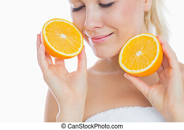Woman with eyes closed holding slices of orange