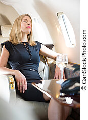 Woman With Eyes Closed Relaxing In Private Jet
