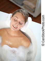 Woman with eyes shut in bathtub