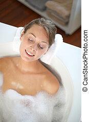 Woman with eyes shut in bathtub