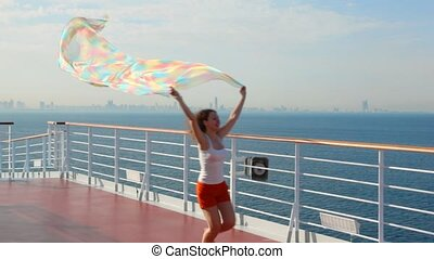 woman with fabric runs on deck of ship