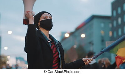 Woman with face mask holding megaphone and rainbow flag. Demonstration against dicrimination . High quality 4k footage