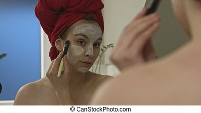 Woman with face mask in mirror