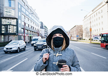 Woman with face mask standing outdoors in city, coronavirus concept.