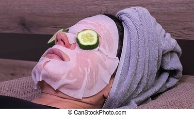 Woman with facial mask and cucumber slices sleeping on the bed