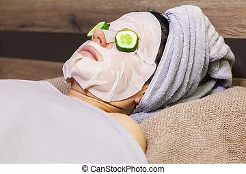 Woman with facial mask and cucumber slices