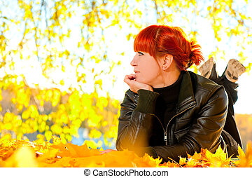 woman with fallen leaves on a sunny day