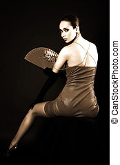 woman with fan in against black background