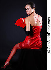 woman with fan in red outfit against black background