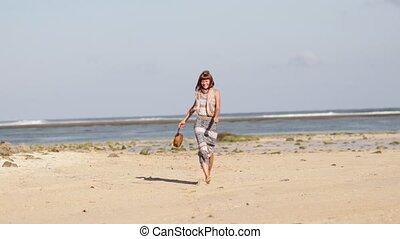 Woman with fashionable stylish nude rattan bag on the beach....