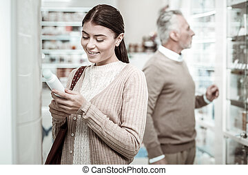Beaming young woman coming to pharmacy store with her loving father