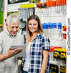 Woman With Father Using Digital Tablet In Hardware Store
