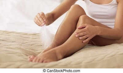 woman with feather touching bare legs on bed - people,...