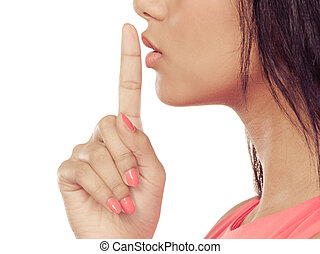 Woman with finger on lips showing silence gesture.