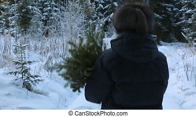 Woman with fir branches walking through the snow forest