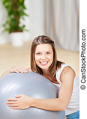 Healthy woman holding a fitball at home