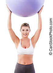 Woman with fitness ball. Attractive mature woman holding fitness ball and smiling at camera