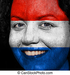 Woman with flag painted on her face to show Netherlands support