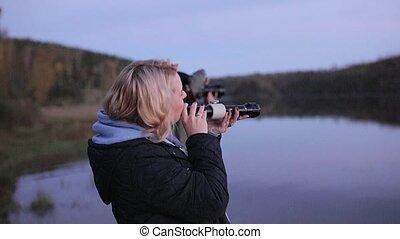 Woman with flashlight near lake