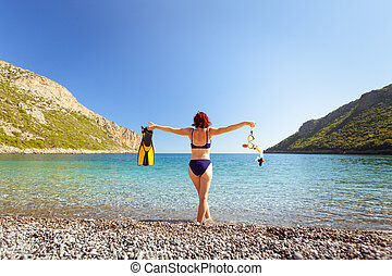 Woman with flippers snorkeling tube on beach