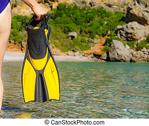 Woman with flippers swimming equipment on beach