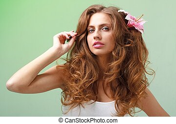 woman with flower against green background