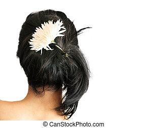 Woman with flower in hair - Back of a young woman with a...