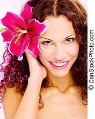 woman with flower in her curl hair