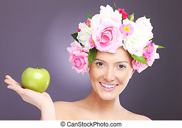 Woman with flowers and green apple