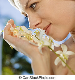 Woman with flowers. - Close up of Caucasian mid-adult woman...