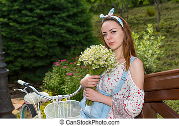 Woman with flowers standing near bike
