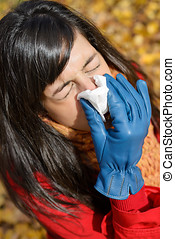 Woman with flu and cold sneezing outdoors