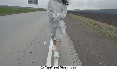 Woman with flying hair on road