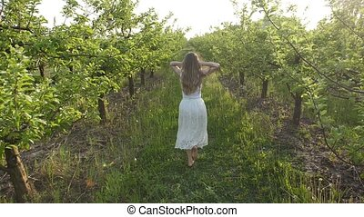 Woman with flying hair running in spring orchard - Carefree...