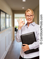 Woman with Folder and Okay Hand Sign In Hallway of House