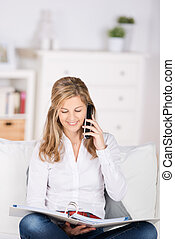 woman with folder using telephone at home