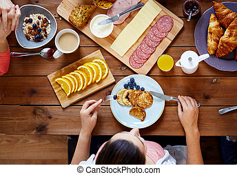 woman with food on table eating pancakes