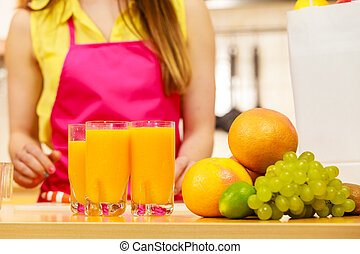 Woman with fresh fruits and juice in kitchen