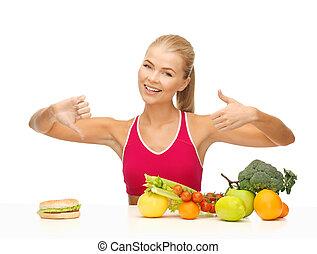 woman with fruits and hamburger comparing food