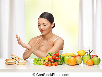 woman with fruits rejecting junk food - healthy and junk...
