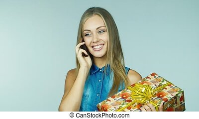 Woman with gift received congratulations by phone