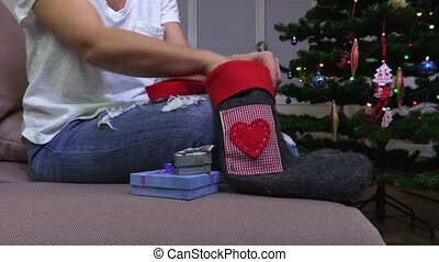 Woman with gifts and Christmas sock near Christmas tree